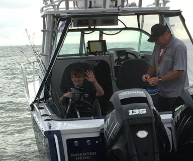 Boy on a fishing boat waving