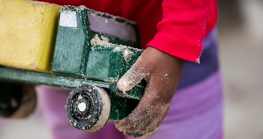Close shot of child carrying sand-encrusted toy truck