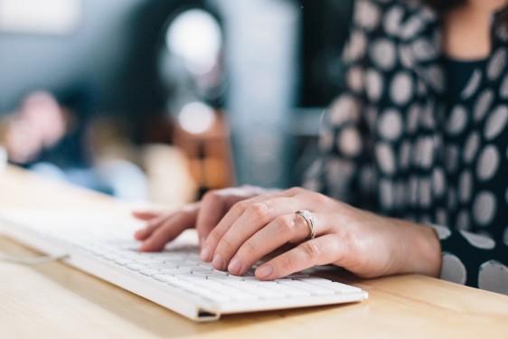 Woman typing at a keyboard