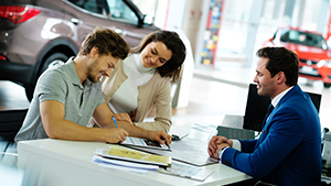 Couple signing papers at a car dealership