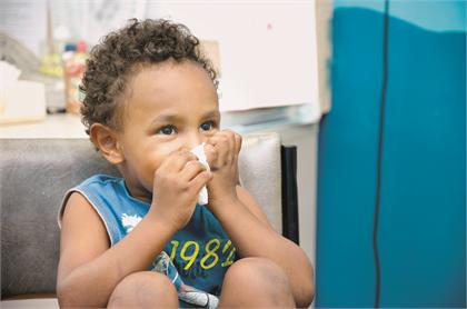 Young child holds tissue to nose