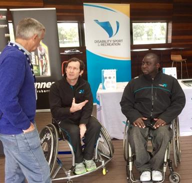 Three men talking. Two of them are in wheelchairs.
