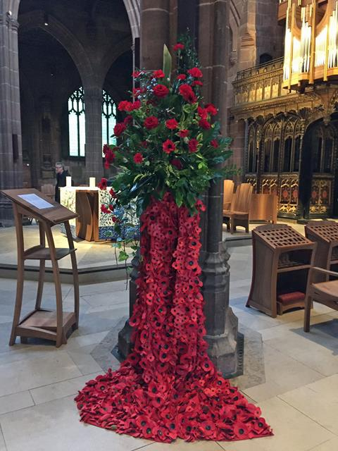 Display of poppies cascading down the pillar with the cathedral organ in the background