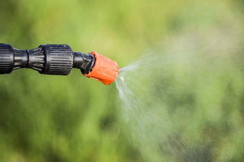 Spraying herbicide from the nozzle of the sprayer manual.