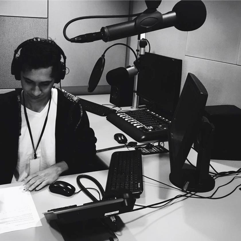 Jacob behind the news desk at NIRS