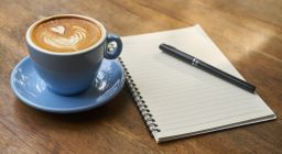 A cup of coffee and a notepad with a pen
