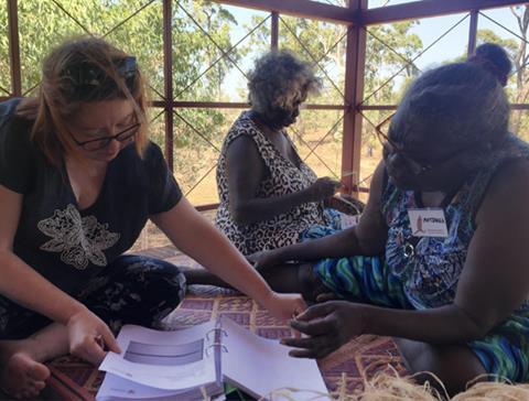Curator Rebecca Conway talking to Director, Matjarra Garrawurra, Bula'bula Arts, Ramingining, 2017. Her mother, master weaver Julie Djulibing Malibirr is working in the background.
