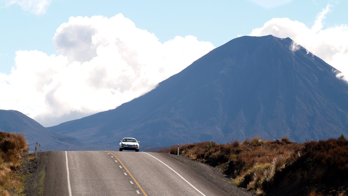 car driving over hill, mountain in background