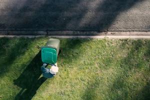 Person taking green waste bin to kerb