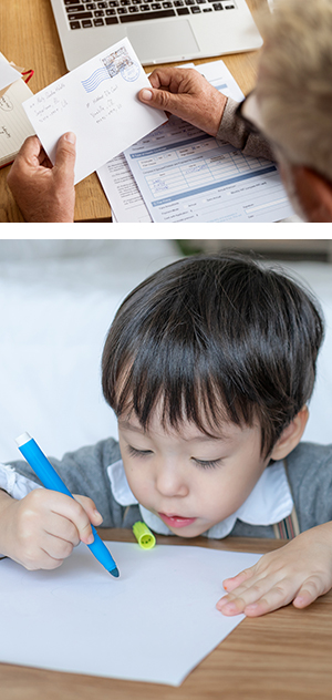 older man reading an envelope; boy writing with a marker