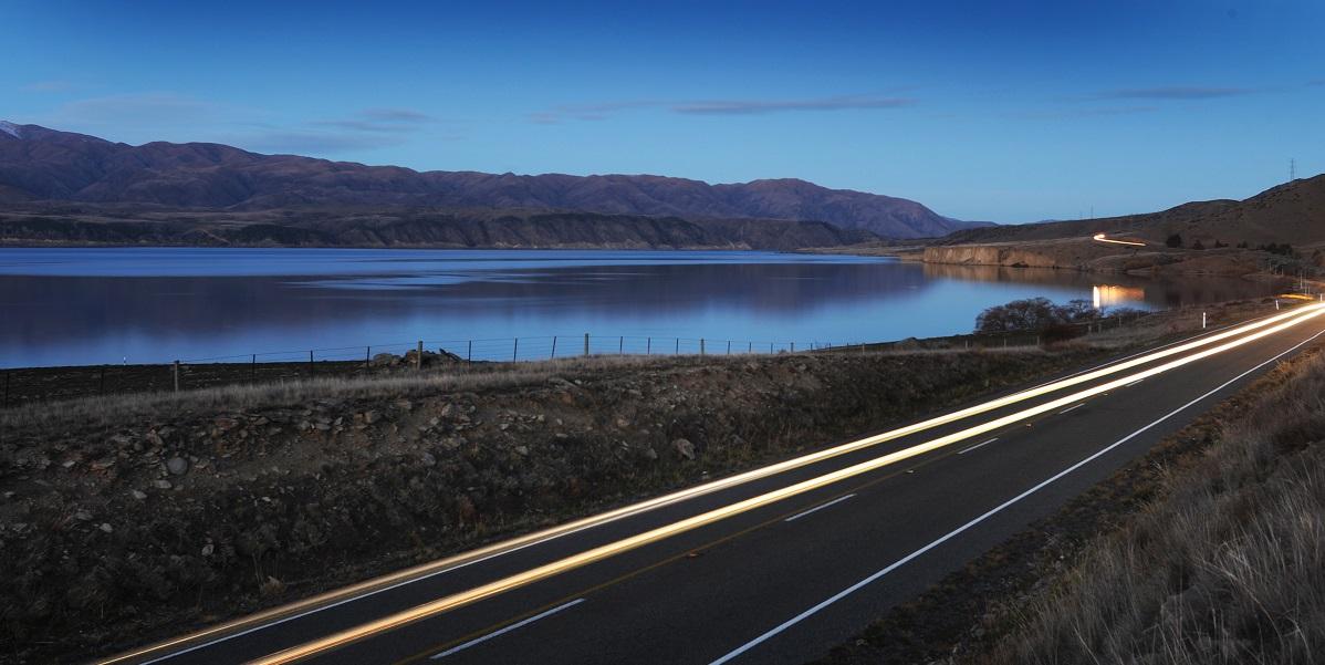 car lights at night on road beside lake