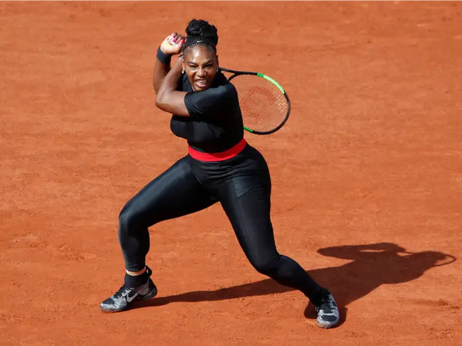 Serena Williams on court swinging in her iconic catsuit