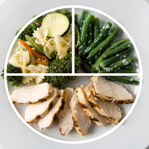Portioned dinner plate with chicken breast, asparagus and pasta salad