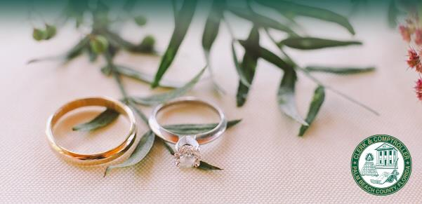 Photo of two wedding rings resting on a table with a spring of flowers and leaves and the Clerk & Comptroller's sealomptroll'ers