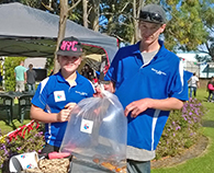 Two employees of Garden Life display our stickers on bags containing sold fish