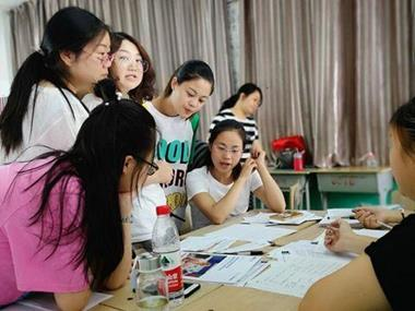 A group of students look at some communicative teaching materials