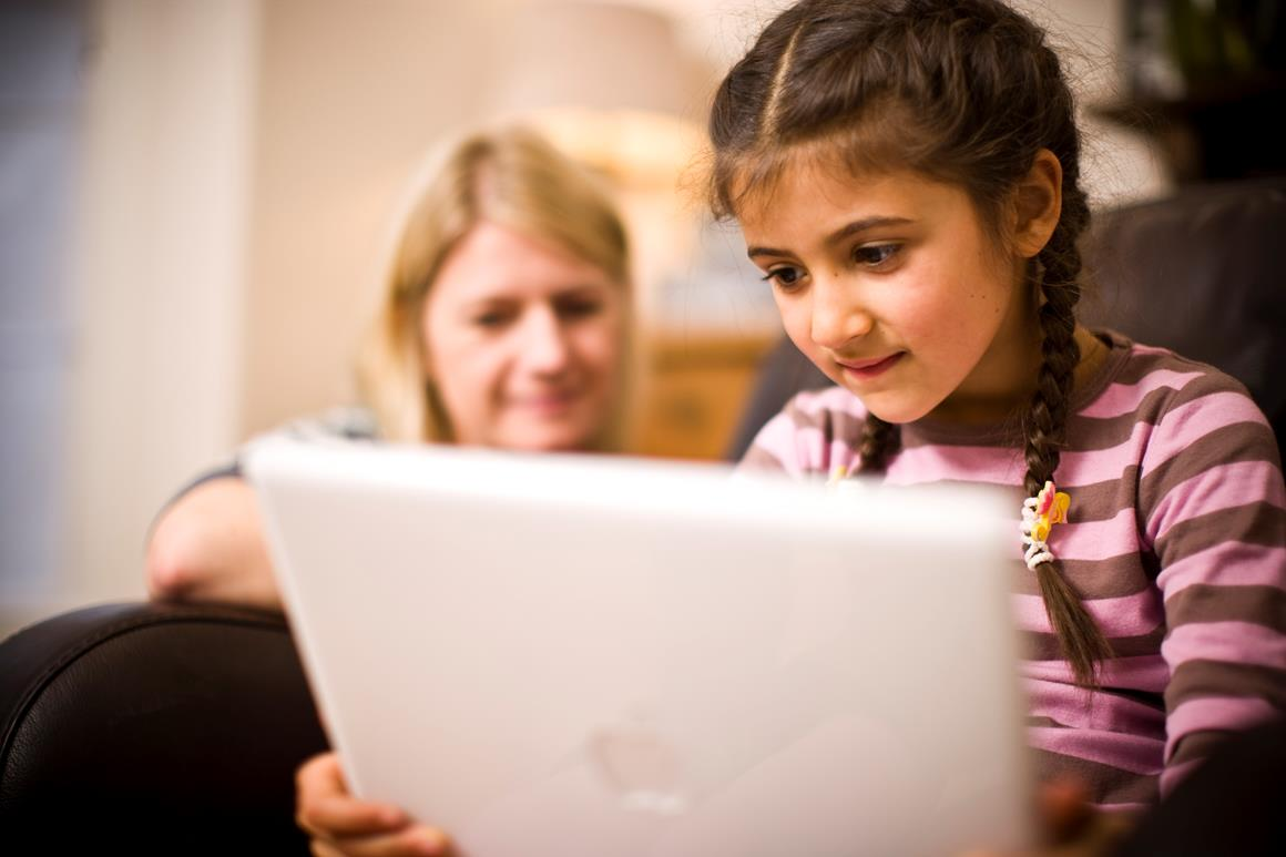 A young girl sits holding an open laptop on her laps and looking at the screen intensely. Behind her there is an adult woman watching her.