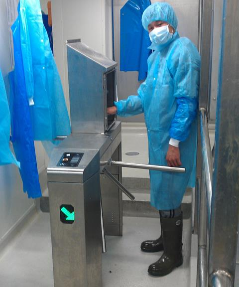 Tristar Turnstile integrated with spray unit - workers must disinfect their hands before being able to access the production area