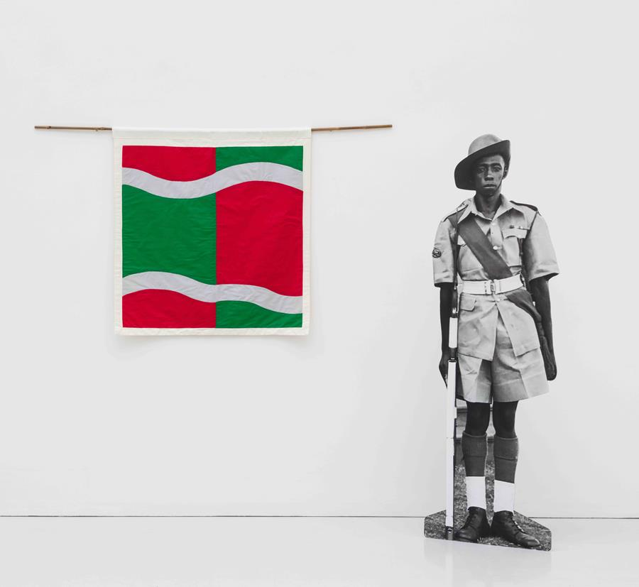 Image description: A colourful square quilt hangs on a white wall, next to a standing cardboard cut-out of a young Black man. The quilt's pattern is made up of blocks of red and green with two horizontal thick white curvy lines. To the right of the quilt is a cardboard cut-out of a black and white photograph of a young Black man in a short-sleeved British colonial military uniform and wide-brimmed hat, holding a rifle. He wears a military sash, high socks, and dark leather boots.