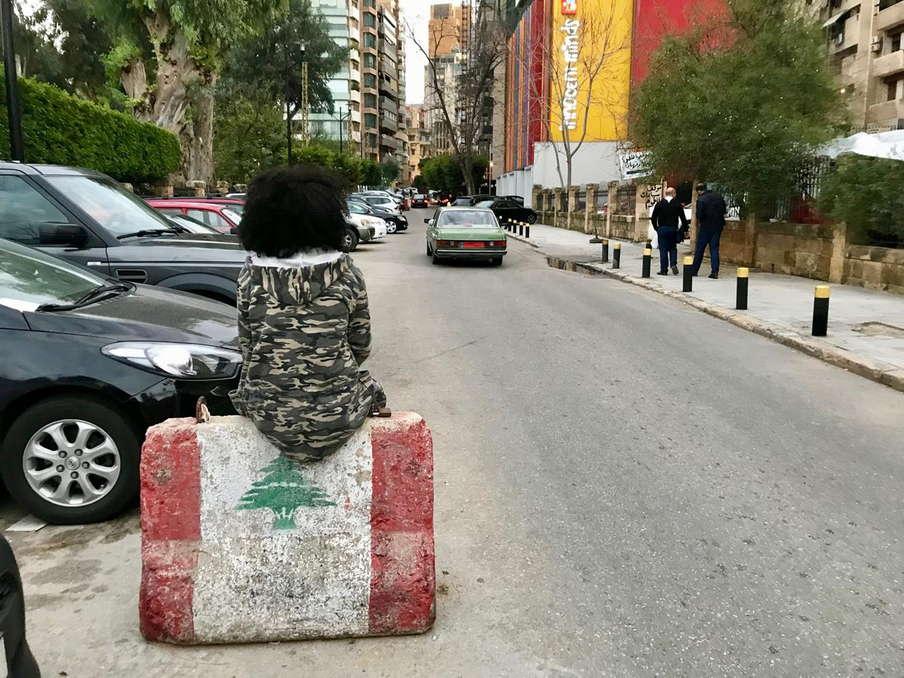 Tsigereda has lived and worked in Lebanon for six years. She perches on a barricade painted with the Lebanese flag in the Hamra neighborhood of Beirut.