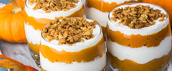Photo of pumpkin spice parfait: pumpkin layers with whipped cream and oat topping.
