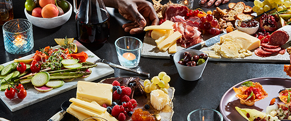 People around a table dressed in several platters of assorted cheeses, meats, fruits, vegetables, crackers, nuts, and cocktails.