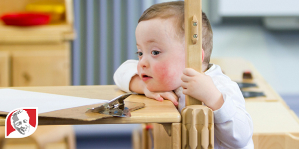 Boy with Down syndrome looking over table graphic