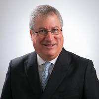 Rent Control expert Richard Green photographed in a portrait style of photo where he is wearing a business suit and smiling.