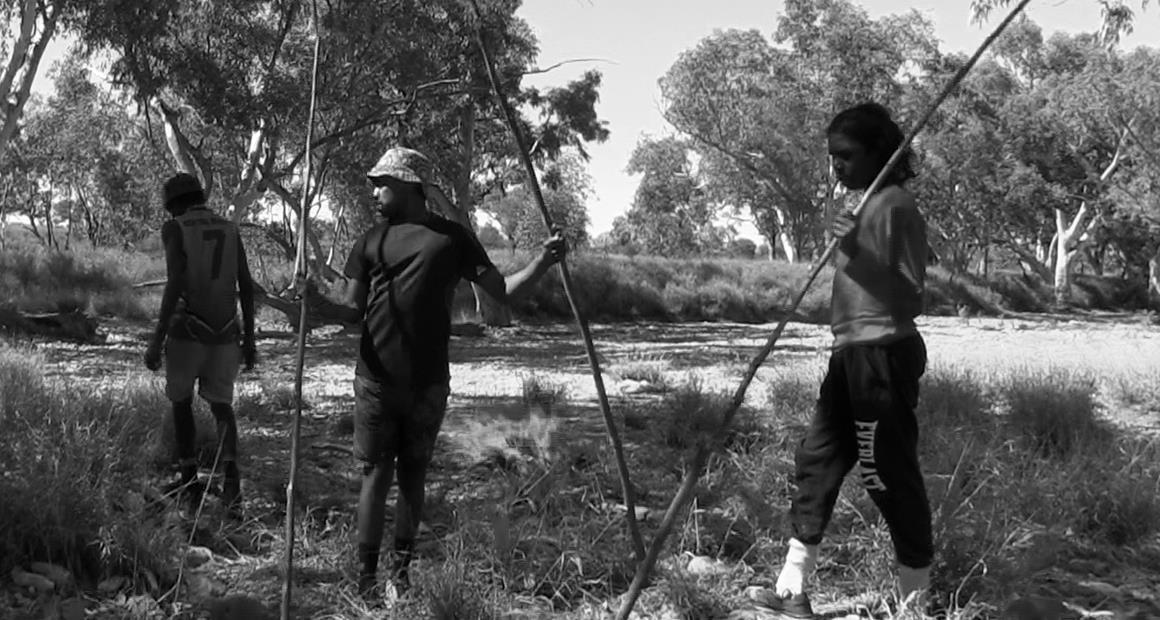 Fellas beginning to straighten their spears in the fire