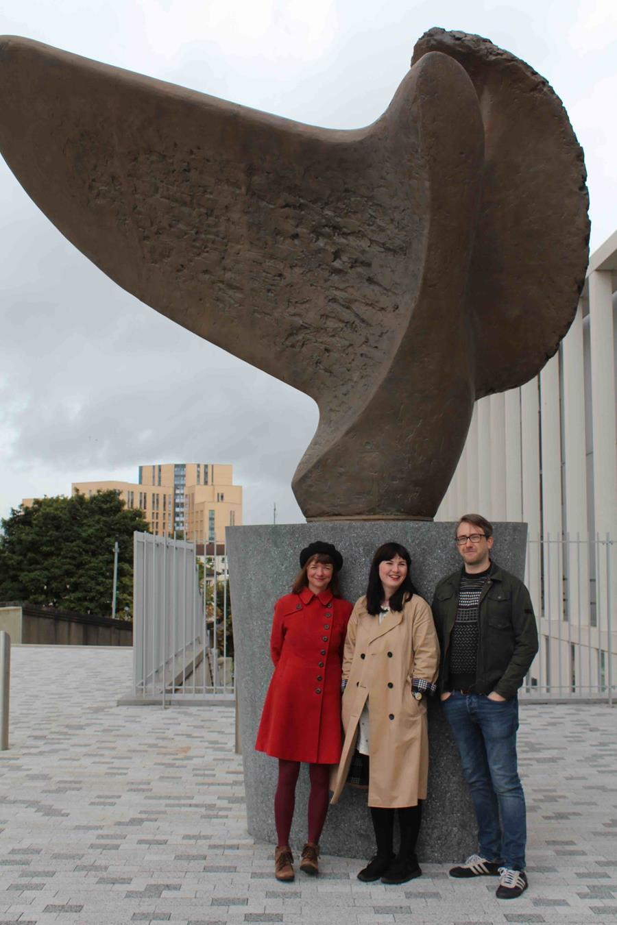 Kate standing next to a sculpture with 2 others