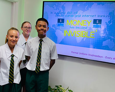 Lockyer District State High School students in front of the TV screen featuring a MoneySmart video.