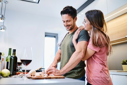 Man and woman cooking food together in the kitchen