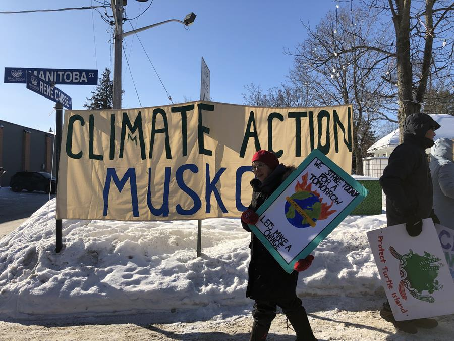 Climate strikers Judy and David in front of Climate Action Muskoka banner in Bracebridge.