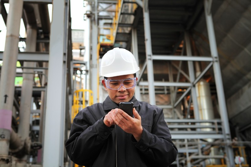 A person wearing in protective hat and goggles using a mobile phone at a construction site.