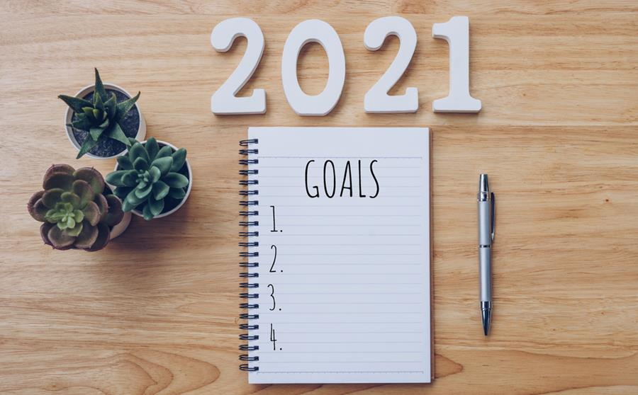 New year 2021 goals list. Office desk table with notebooks and pencil with potted plant.